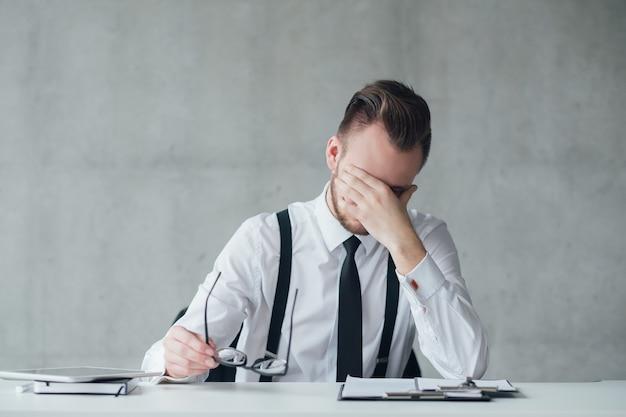 Büroalltag und fristen. porträt des gestressten jungen managers, der am schreibtisch sitzt. platz kopieren.