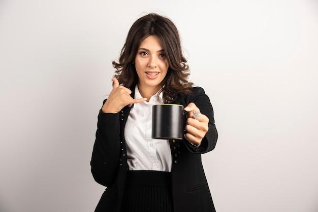 Büroangestellte bietet eine tasse tee an und gestikuliert, sie anzurufen