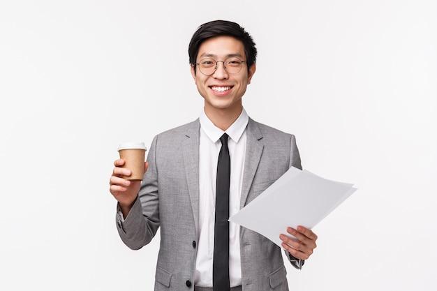 Büroangestellte, business- und lifestyle-konzept. taille porträt des optimistischen, enthusiastischen jungen asiatischen geschäftsmannes, der morgenkaffee im büro trinkt, erfreut erfreut, dokumente zu halten