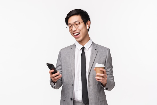 Büroangestellte, business- und lifestyle-konzept. taillenporträt des glücklichen fröhlichen asiatischen männlichen unternehmers, der freund mit drahtlosen kopfhörern anruft, smartphone hält und kaffee zum mitnehmen, lächelnd