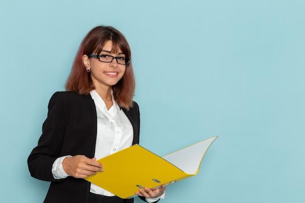 Büroangestellte der vorderansicht, die gelbe datei auf der blauen oberfläche liest und hält