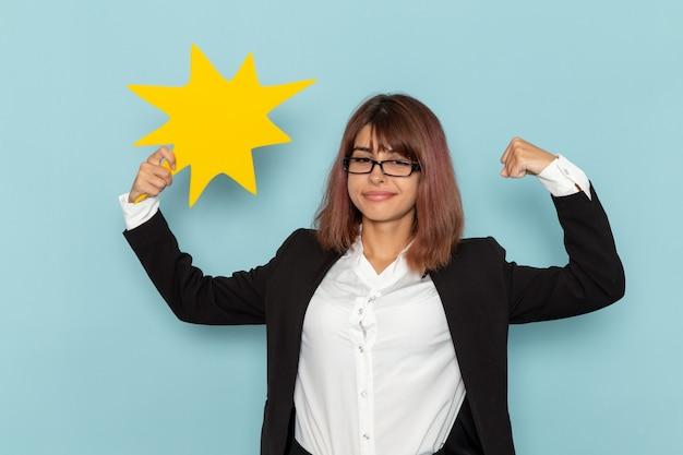Büroangestellte der vorderansicht, die gelbes zeichen hält und auf der blauen oberfläche biegt