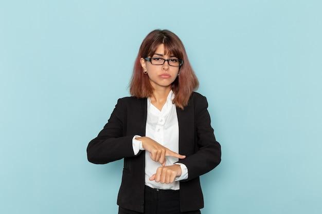 Büroangestellte der vorderansicht, die ihr handgelenk auf der blauen oberfläche hervorhebt
