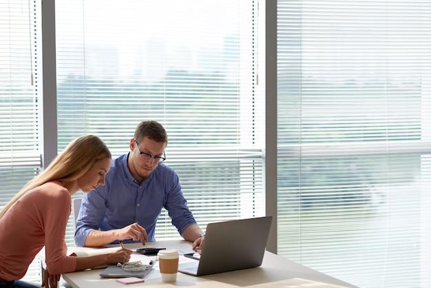 Büroangestellte, die am projekt im geräumigen büro zusammenarbeiten