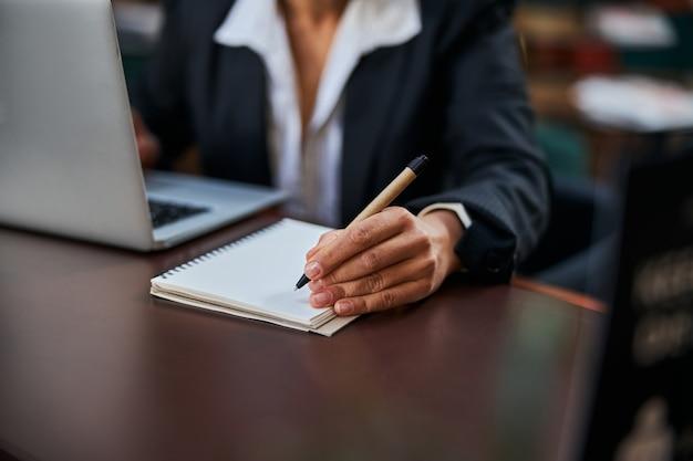 Büroangestellte, die an ihrem arbeitsplatz sitzt und sich während des online-meetings notizen macht