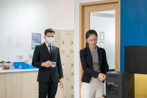 Büroangestellte, die in der warteschlange der sozialen distanz stehen, um einen kaffee aus der kaffeemaschine zu kochen