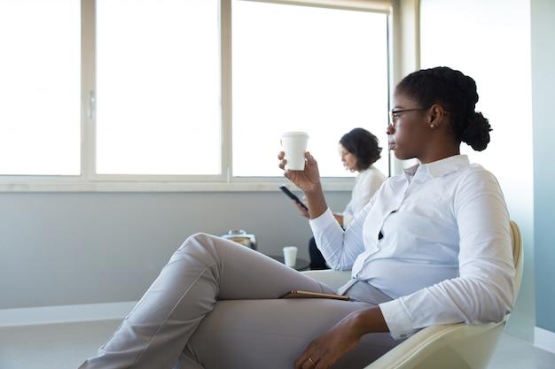 Büroangestellte, die kaffee in der bürolounge trinken