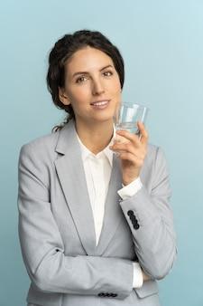 Büroangestellte geschäftsfrau hält glas wasser und erinnert daran, mineralwasser am arbeitsplatz zu trinken