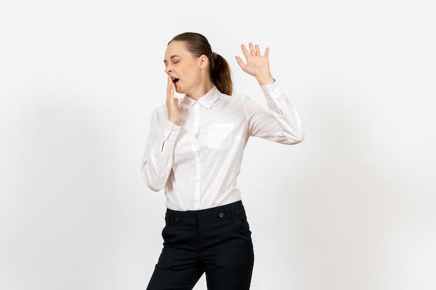 Büroangestellte in eleganter weißer bluse, die auf weiß gähnt