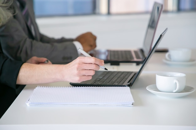 Büroangestellte schreiben notizen, laptop mit tisch mit tassen kaffee. nahaufnahme der hände, beschnittener schuss. bildungs- oder digitales kommunikationskonzept
