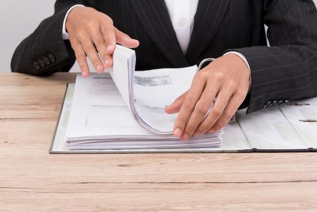 Büroangestellter behandelt dokumente auf dem schreibtisch.