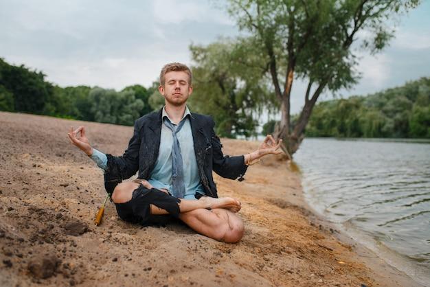 Büroangestellter, der am strand in der yoga-pose, einsame insel sitzt. geschäftsrisiko, zusammenbruch oder insolvenzkonzept