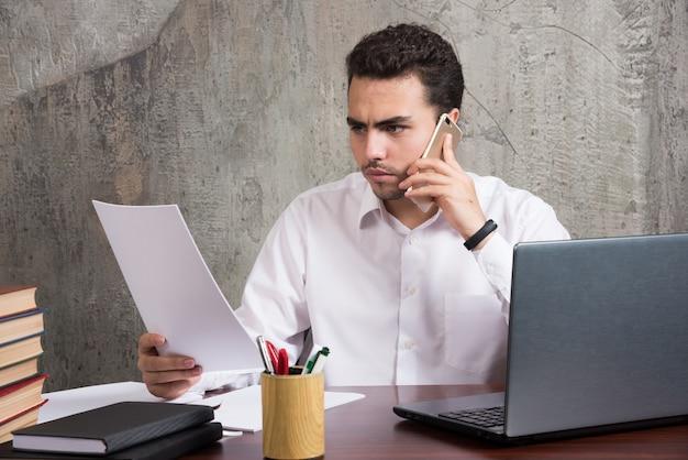 Büroangestellter, der auf zelle spricht und blätter von papieren hält. hochwertiges foto