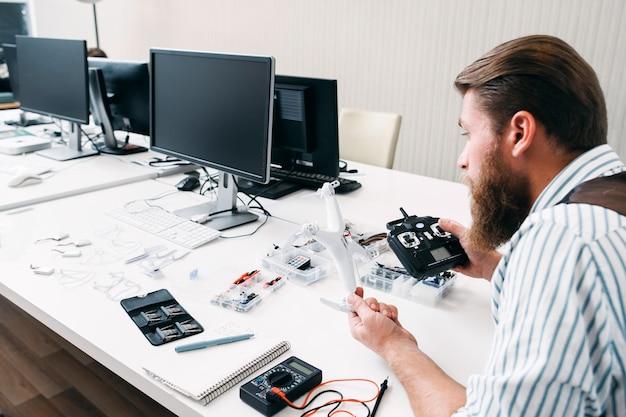 Büroangestellter, der drohne bei der arbeit zusammenbaut. bärtiger mann, der im offenen raum mit quadrocopter und werkzeugen sitzt und elektronisches spielzeug baut
