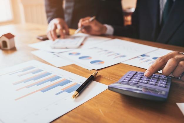 Büroangestellter, der hilft, finanzdokumente und finanzdiagramme im büro zu überprüfen