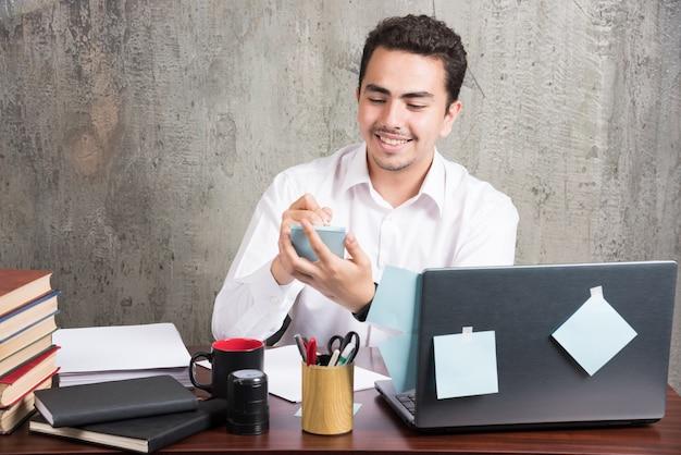 Büroangestellter, der mit telefon am schreibtisch spielt.