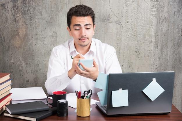 Büroangestellter, der sein telefon am schreibtisch betrachtet.