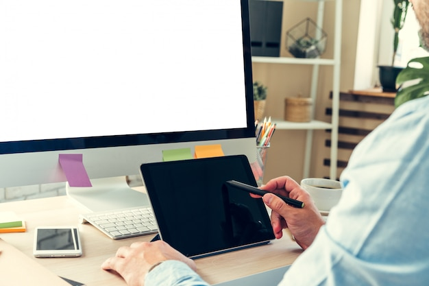 Büroangestellter, der seine arbeit erledigt, an seinem arbeitstisch mit einem computer sitzend