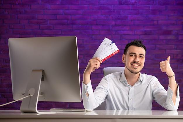 Büroangestellter der vorderansicht, der hinter seinem arbeitsplatz sitzt und tickets hält