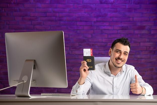 Büroangestellter der vorderansicht, der hinter seinem arbeitsplatz sitzt und tickets und reisepass hält
