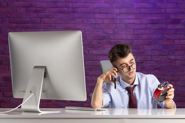 Büroangestellter der vorderansicht hinter dem schreibtisch, der spricht Premium Fotos