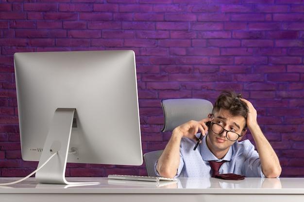 Büroangestellter der vorderansicht hinter dem schreibtisch, der spricht