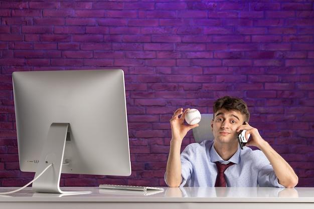 Büroangestellter der vorderansicht hinter schreibtisch, der baseballball hält und am telefon spricht
