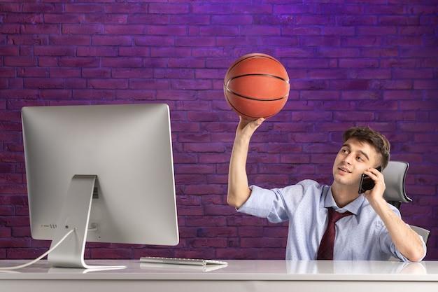 Büroangestellter der vorderansicht hinter schreibtisch, der basketball hält und am telefon spricht