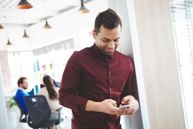 Büroangestellter, der während der arbeit mit dem handy chattet