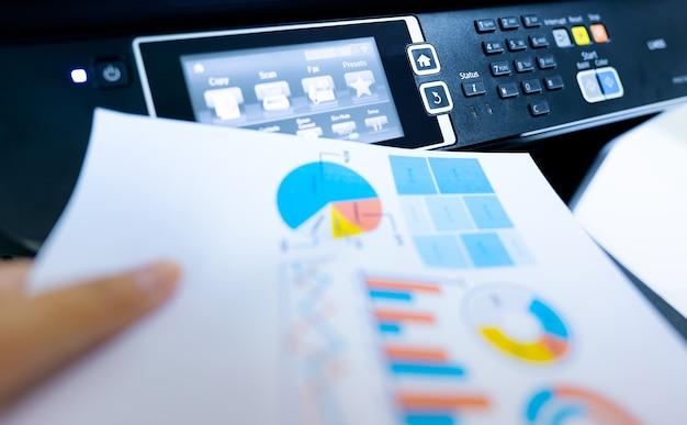 Büroangestellter druckpapier auf multifunktionslaserdrucker. kopieren, drucken, scannen und faxen sie im büro. moderne drucktechnologie. fotokopierer. dokumenten- und papierarbeit. scanner. sekretariatsarbeit.