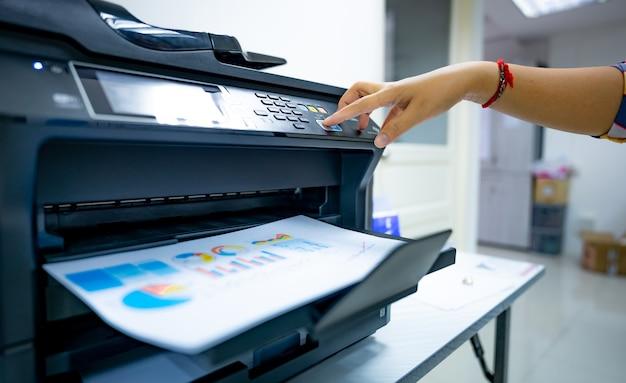 Büroangestellter druckt papier auf multifunktionslaserdrucker. kopieren, drucken, scannen und faxen sie im büro. dokumenten- und papierarbeit. drucktechnologie. handpresse auf fotokopiergerät. scanner-ausrüstung.