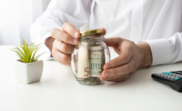 Büroangestellter hält ein glas mit geld und schließt mit der hand. einsparungskonzept.