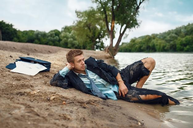Büroangestellter im zerrissenen anzug, der auf dem strand auf verlorener insel ruht. geschäftsrisiko, zusammenbruch oder insolvenzkonzept