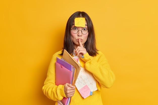 Büroangestellter mit aufkleber auf der stirn macht stille geste hält ordner trägt runde brille und pullover.