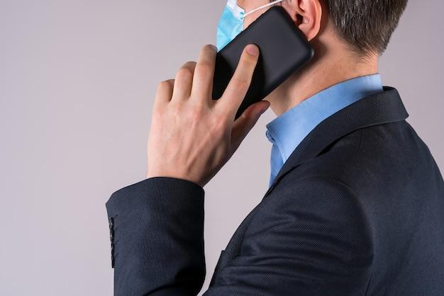 Büroangestellter mit handy in der schutzmaske auf grauer wand