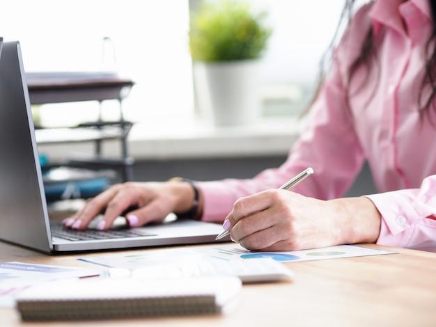 Büroangestellter schreibt notizen und druckt auf laptop
