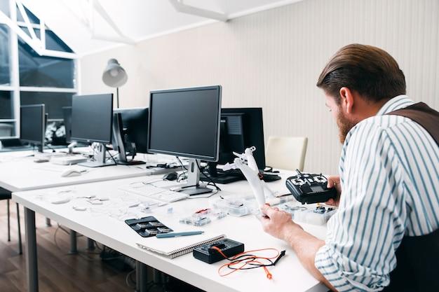 Büroangestellter sitzt spät bei der arbeit mit drohne. aufgeregt vom neuen elektronischen spielzeugmann. hobby, freizeit, unterhaltung, begeisterung, leidenschaft konzept