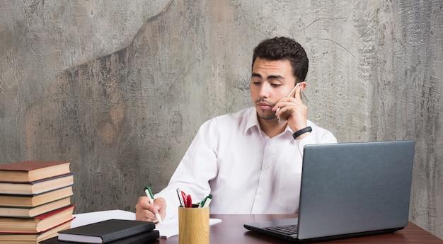 Büroangestellter spricht in der zelle und schreibt etwas in blätter. hochwertiges foto