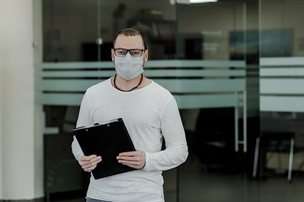 Büroangestellter trägt maske sitzendes büro