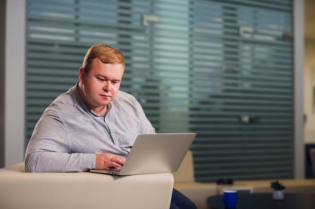 Büroarbeitskonzept. der mann stöbert an seinem laptop und sitzt im büro auf einem gemütlichen weißen sofa