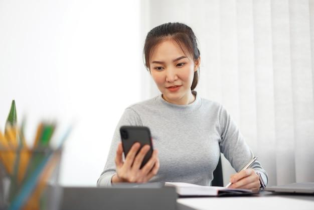 Büroarbeitskonzept eine beamtin, die ein mobiltelefon verwendet, um die sitzungsagenda zu überprüfen