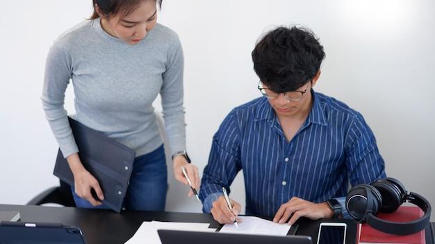 Büroarbeitskonzept eine hübsche geschäftsfrau, die von ihrem geschäftspartner nach einer idee zu den marketingstrategien fragt.