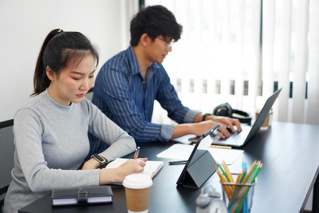 Büroarbeitskonzept zwei geschäftsleute, die mit zwei tassen kaffee im büro an den geräten arbeiten.