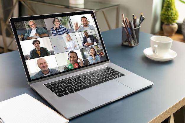 Büroarbeitsplatz. auf dem laptopbildschirm nehmen personen an einer videokonferenz, einem virtuellen meeting, einem online-geschäftskonzept teil