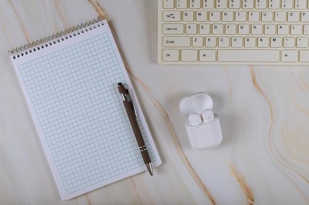 Büroarbeitsplatz mit computertastatur und drahtlosem kopfhörernotizbuch, stift, der blogging tabelle bearbeitet