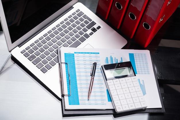 Büroarbeitsplatz mit dokumenten und briefpapier nahe roten ordnern
