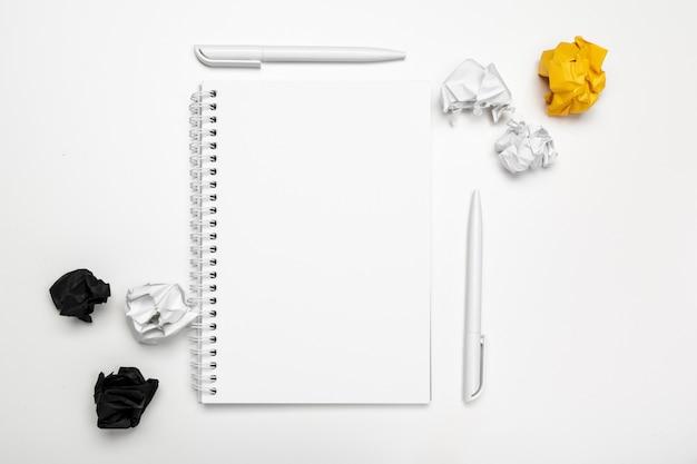 Büroarbeitsplatz mit einem leeren notizbuch und einem zerknitterten papier