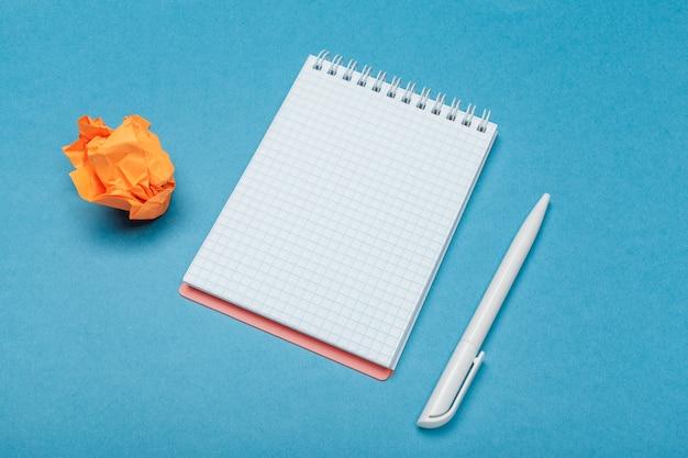 Büroarbeitsplatz mit einem leeren notizbuch, zerknittertes papier