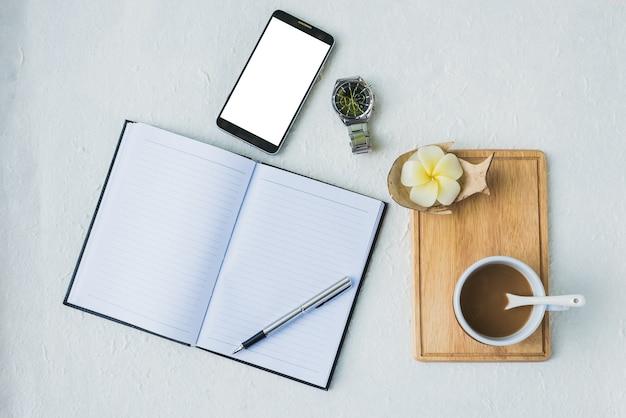 Büroarbeitsplatz mit kalenderbuch, tasse kaffee, uhr, medizin und moblie konzept
