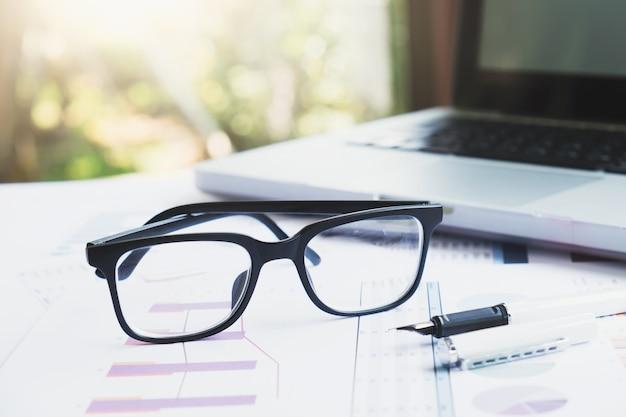 Büroarbeitsplatz mit laptop und gläser auf holztisch.